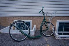 La vista al aire libre de las bicis del rodillo de Amish o las vespas se inclina contra una casa fotos de archivo libres de regalías
