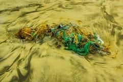 La vista all'aperto dell'immondizia nella spiaggia, ogni giorno, spreco delle corde e della rete da pesca si accumula sulla spiag Immagini Stock
