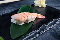 La vista alta vicina sopra ha servito Nigiri con gamberetto sul piatto scuro su fondo scuro con lo spazio della copia Sushi di co fotografia stock libera da diritti