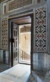 La vista angulosa de una puerta abierta adornada envejecida de madera que llevaba a un paso con la luz brillante, color adornó la Foto de archivo libre de regalías