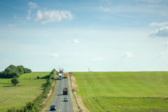 La vista aérea de los coches del ith de la carretera, camiones pone verde campos y el windmil Imagen de archivo