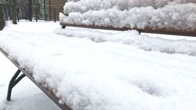 La vista ascendente cercana de un banco nevoso del invierno en un parque, nieve está bajando y gente irreconocible que caminan a  metrajes