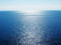 La vista blu del mare ionico con il sole irradia sull'isola di Corfù immagini stock