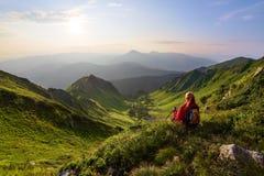La vista con le alte montagne rocciose Una ragazza si siede sull'erba verde fra i fiori Raggi di Sun Belle nubi Immagine Stock Libera da Diritti