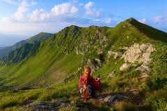 La vista con le alte montagne rocciose Una ragazza si siede sull'erba verde fra i fiori Raggi di Sun Paesaggio di ESTATE Fotografia Stock Libera da Diritti