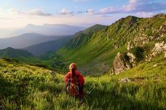 La vista con le alte montagne rocciose Una ragazza si siede sull'erba verde fra i fiori Raggi di Sur Paesaggio di estate Fotografie Stock Libere da Diritti