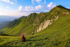La vista con le alte montagne rocciose Una ragazza si siede sull'erba verde fra i fiori Raggi di Sur Paesaggio di ESTATE Immagine Stock Libera da Diritti