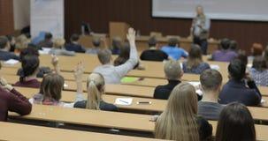 La vista da dietro di grande gruppo misto di etnia di studenti in un'aula, ascoltante come loro insegnante tiene una conferenza archivi video