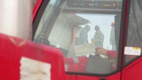 La vista da parte a parte ha bisogno il vetro della cabina dei lavoratori maschii lavoranti in uniforme ed in caschi archivi video
