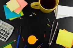 La vista da tavolino della tavola dell'ufficio con l'insieme dei rifornimenti variopinti, il blocco note in bianco bianco, la taz Fotografie Stock