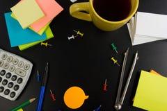 La vista da tavolino della tavola dell'ufficio con l'insieme dei rifornimenti variopinti, il blocco note in bianco bianco, la taz Immagine Stock