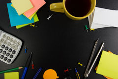 La vista da tavolino della tavola dell'ufficio con l'insieme dei rifornimenti variopinti, il blocco note in bianco bianco, la taz Fotografia Stock