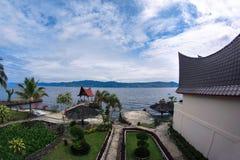 La vista da una finestra alla casa ed il giardino radrizzano alla riva del lago Fotografia Stock