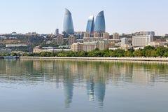 La vista dal mar Caspio sulla fiamma si eleva grattacieli a Bacu Fotografia Stock