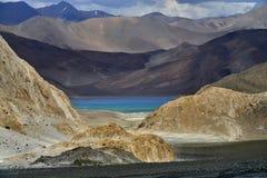 La vista dal passaggio al lago sacro del TSO di Pangong: l'alta montagna gialla e marrone crea una ciotola e un interno di pietra Fotografia Stock Libera da Diritti