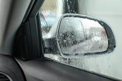 La vista dall'interno dell'automobile, esaminante lo specchio laterale, ha bagnato dall'acqua immagini stock