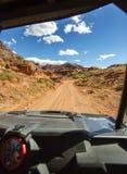 La vista dall'interno fuori del veicolo stradale Rim Road Utah bianco trascina avanti diritto Fotografie Stock