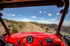 La vista dall'interno fuori del veicolo stradale Rim Road Utah bianco trascina avanti diritto un giorno soleggiato Immagini Stock