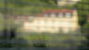 La vista dalla finestra su una retro casa gialla attraverso i ciechi video d archivio