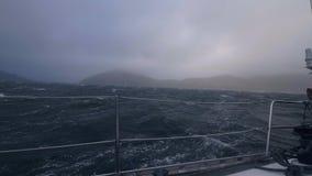 La vista dalla navigazione dell'yacht del bordo sul mare tempestoso ondeggia Barca a vela che oscilla sulle onde stock footage