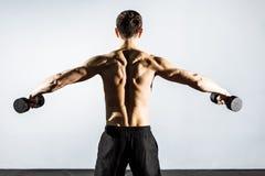 La vista dalla parte posteriore Uomo muscolare che fa gli esercizi con le teste di legno fotografia stock libera da diritti