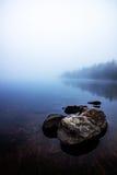 La vista dalla riva di una nebbia ha coperto il lago Immagini Stock