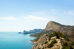 La vista dalle altezze delle montagne, del mare e del cielo blu con le nuvole bianche immagine stock libera da diritti