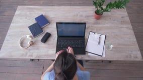 La vista de arriba del texto que mecanograf?a de la muchacha del freelancer en el teclado del ordenador port?til y escribe notas  almacen de video