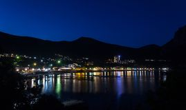 La vista de la bahía del Mar Negro entre las montañas con las luces de la ciudad refleja Foto de archivo