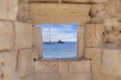 La vista de dos barcos en el mar pensó la ventana medieval del castillo viejo Imagen de archivo