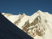 La vista de la cara norte del Tau de Dykh del soporte en luz del sol de la mañana con una cumbre y una luna claras arriba Foto de archivo libre de regalías