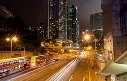 La vista de la ciudad y del movimiento de la noche alinea en el camino oscuro con los autobuses y las estructuras urbanas Imagen de archivo