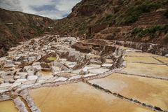 La vista de la sal acumula, Maras, Perú, Suramérica con el cielo azul nublado fotografía de archivo libre de regalías