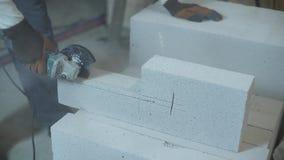 La vista de las manos del constructor que cortaban el bloque de cemento aireado con la circular consideró almacen de video