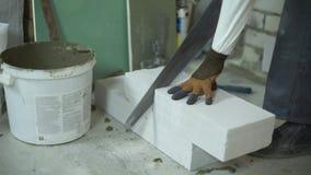La vista de las manos del constructor que cortaban el bloque de cemento aireado con la mano consideró almacen de metraje de vídeo