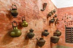 La vista de los buques de cobre amarillo antiguos de la cocina montó en un muro de cemento, Chennai, la India, el 25 de febrero d fotografía de archivo libre de regalías