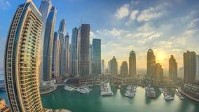 La vista de los rascacielos modernos que brillan en salida del sol enciende el timelapse en el puerto deportivo de Dubai en Dubai metrajes