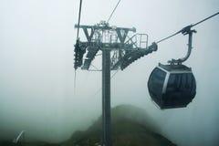 La vista de la montaña y funicular superiores con una cabina, están nublados también se empañan Foto de archivo libre de regalías