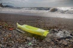 La vista de la playa de Genoa Sturla devasted después de la tormenta de la noche antes Aquí una canoa destruida dejada en la oril fotografía de archivo
