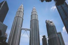 La vista de la torre gemela de Petronas y Maxis se elevan en Kuala Lumpur, Malasia Imagen de archivo