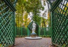 La vista degli alberi di autunno e la statua di marmo antica di estate fanno il giardinaggio Fotografia Stock