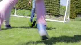 La vista dei piedi come nonno ed i nipoti giocano a calcio archivi video