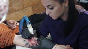 La vista del amo femenino del tatuaje profesional está pintando con la tinta, haciendo la cubierta Trabajos en guantes estéril de metrajes