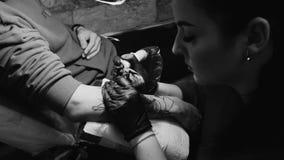 La vista del amo femenino del tatuaje profesional está pintando con la tinta, haciendo la cubierta Trabajos en guantes estéril de almacen de metraje de vídeo