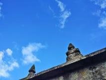 La vista del cielo blu da una parete di pietra del vecchio granito gallego ha incoronato dai culmini immagine stock