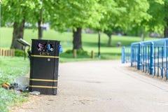 La vista del giorno ha sovraffollato riempito troppo con il cestino per i rifiuti dei rifiuti del metallo del nero dei rifiuti Fotografia Stock