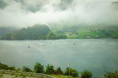 La vista del lago Lungern con le barche e la mattina annebbiano e si appannano in autu immagine stock libera da diritti