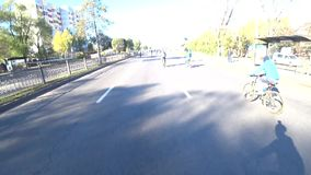 La vista del manillar de la bicicleta pasa a la vista del camino con los ciclistas Acontecimiento deportivo almacen de video