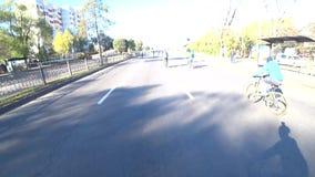 La vista del manubrio della bicicletta passa alla vista della strada con i ciclisti Evento sportivo archivi video