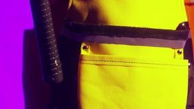 La vista del martello con la maniglia rossa e nera di gomma ha messo nel grembiule giallo del ` s del carpentiere video d archivio